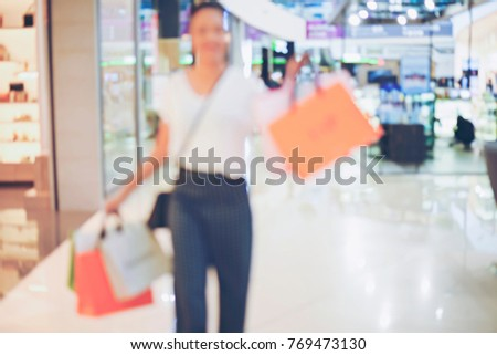 Abstact blurred Happy woman enjoying with shopping bags shopping mall department store background.