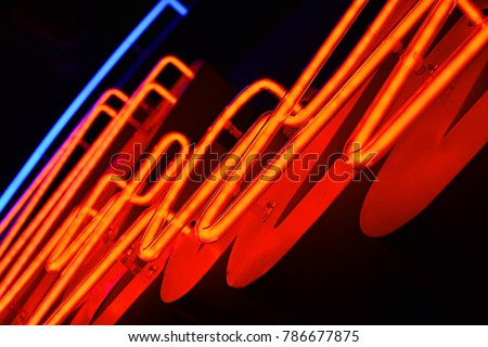 Abstact red neon sign with a blue neon tube in the background #786677875