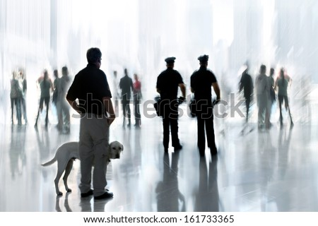 abstakt image of people and security guard with a dog in the lobby of a modern business center with a blurred background