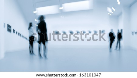 abstakt image of people in the lobby of a modern art center with a blurred background and a blue tonality