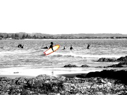 Abstract - A surfer carries a twin fin surfboard into the ocean. The surroundings are monochrome but the colours on the surfboard are bold and stand out