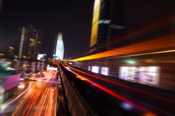 Abstract acceleration speed motion light Blur from Sky Train at night in modern city (background)