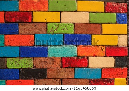 abstract aged multicolored painted baked earthen clay brick blocks, colorful architectural structure design, exterior wall background, wallpaper, backdrop