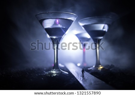 Abstract alcoholism concept. Silhouette of a man standing in the middle of the road on a misty night with giant glasses filled with alcoholic beverage. Creative artwork decoration #1321557890