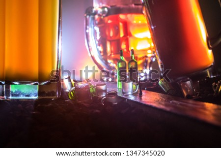 Abstract alcoholism concept. Silhouette of a man standing in the middle of the road on a misty night with giant glasses filled with alcoholic beverage. Creative artwork decoration #1347345020