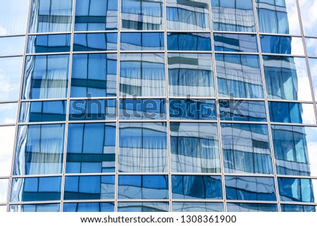 Abstract architecture background. Sky and building are reflected in the office skyscraper facade. Concept of modern urban constructions and business. Reflections of a city in glass windows. #1308361900