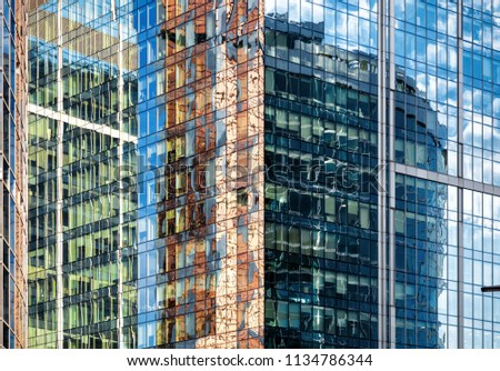 Abstract architecture background. Sky and buildings are reflected in the office skyscraper facade. Concept of modern city constructions and business. Bizarre urban reflections in glass windows. #1134786344