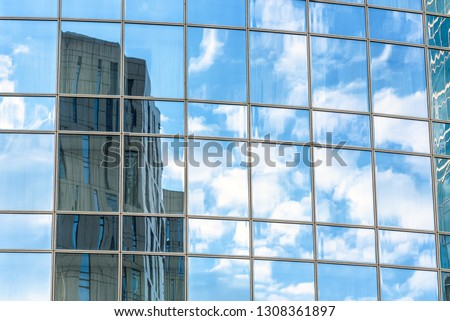 Abstract architecture background. Sky and buildings are reflected in the office skyscraper facade. Concept of modern urban constructions and business. Reflections of a city in glass windows. #1308361897
