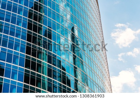 Abstract architecture background. Sky and buildings are reflected in the office skyscraper facade. Concept of modern urban constructions and business. Reflections of a city in glass windows. #1308361903