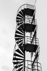Abstract architecture fragment, old outdoor metal spiral ladder on the wall, black and white photo