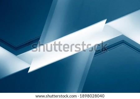 Abstract architecture surfaces of walls, ceiling and window. Futuristic interior fragment in blue. Polyhedron geometric background structure with multiple facets of various shapes glowing in darkness. Zdjęcia stock ©