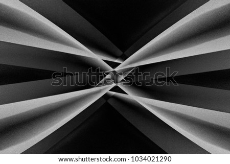Abstract architecture with distortion effect. Angular girders refracted by small glass prism in center of composition. Contrast black and white photo of modern building in darkness.