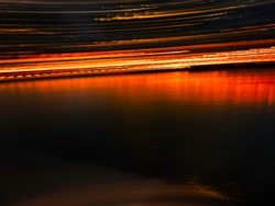 Abstract arena of slanted panning light trails and reflections over seawater in Boston Harbor