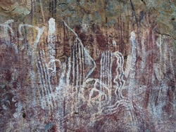 Abstract art from Australian Aboriginals, damaged with water and wind, paintings are on a granite wall, recorded to be over 10,000 years old.