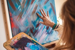 Abstract art paintings. Woman artist painting on canvas by hand and finger. Female artist using creative skill and technique