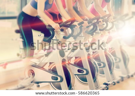 Abstract background against low section of people working out at spinning class