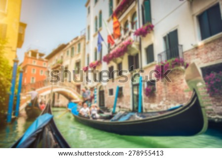 Abstract background blur bokeh image of traditional Gondolas on historic canal on a sunny day in Venice, Italy with pastel toned retro vintage Instagram style filter and lens flare effect