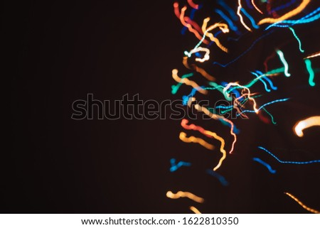 Abstract background for wallpaper. Many multi-colored lines. Long exposure garland shot.