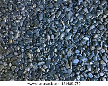 Abstract background from black pebbles pattern on the beach. Travel and summer background concept.