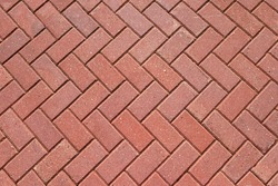Abstract background from paving red tiles, bricks. Top view of the pavement pattern. Concept for construction, urban environment improvement, finishing works, landscape design.