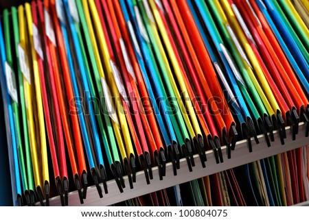 Abstract background image of colorful hanging file folders in drawer.  Macro with with extremely shallow dof.  Selective focus in front edges of files.