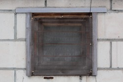 Abstract background in the form of a wooden window behind a metal protective grille and mosquito net on a white brick background.