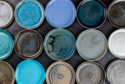 abstract background made of decorative empty round ceramic dishes different colors, plates in the pottery workshop, handwork, top view