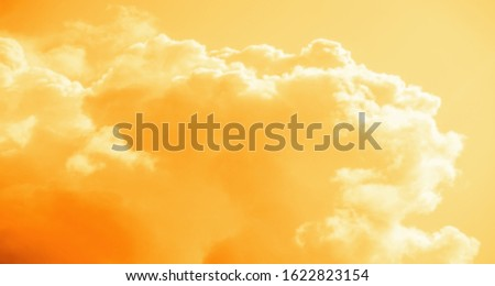 Abstract background of beautiful cumulus clouds in the sky, orange tinted.