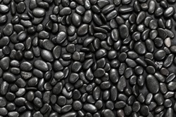Abstract background of black pebble stones arranged on black surface