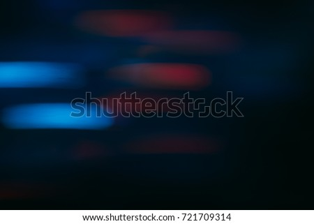 Abstract background of colorful blurs in motion on black. Bokeh of defocused streaks, blurred neon blue and red leds, glowing city lights and traffic, wallpapers and banners