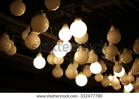 Abstract background of many hanging light bulbs in the dark room. (Selective focus, blur out the some light bulbs for aesthetic quality)
