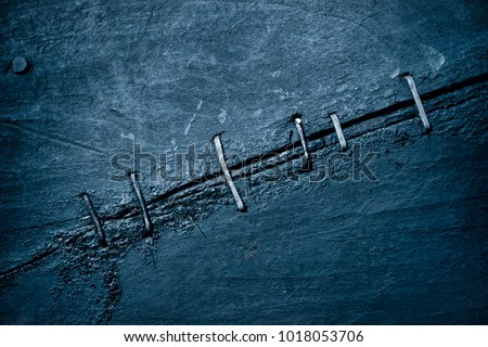 Abstract background of old tarred wooden planks of the old boat fastened together with Iron cramps fasteners  Tinted blue #1018053706