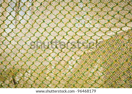 Abstract background of openframe knotted yellow green netting used by trawlers as a fishing net when deep sea fishing