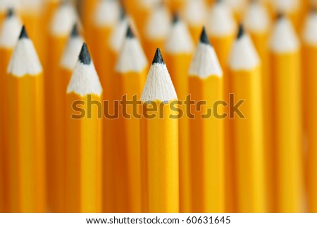 Abstract background of yellow pencils with extremely shallow dof.  Selective focus limited to front pencil.