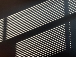 Abstract background on Parallel diagonal black and white gradient lines. Sun shutters shadow on wallpaper. Light and shade play from window at home.