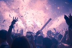 Abstract Background Party Concert Concept. Party people concept. Crowd happy and joyful in club. Celebration, festival, Happiness,  Blurry night club .Event Show concert  EDM on stage.