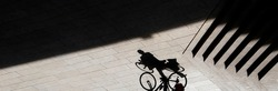Abstract background shadow silhouette of a person climbing a bike next to outdoor stairs, high contrast sepia black and white