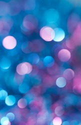 Abstract background spherical bokeh of colourful festive lights in shades of blue, turquoise and violet.