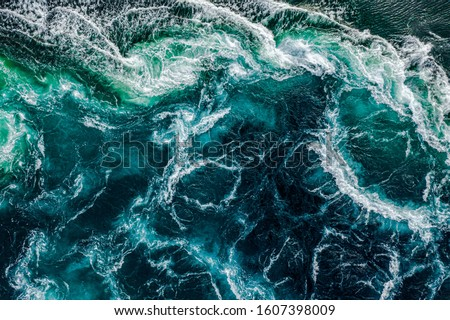 Photo of  Abstract background. Waves of water of the river and the sea meet each other during high tide and low tide. Whirlpools of the maelstrom of Saltstraumen, Nordland, Norway