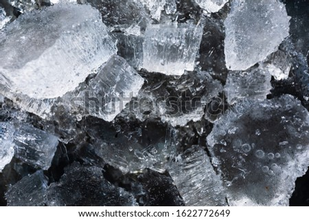 Abstract background with broken pieces of ice of natural origin on a dark background.