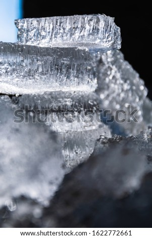 Abstract background with broken pieces of natural ice on a dark background tower lined.