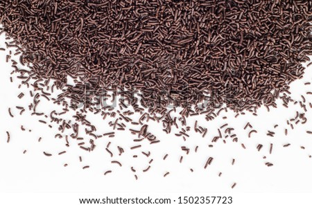 Abstract background with chocolate sprinkles raining down on white - cake topping sprinkles top view