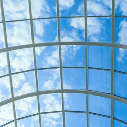 abstract background with glass ceiling elements in a modern building. view of the blue sky through a glass window, separated by lattice elements.