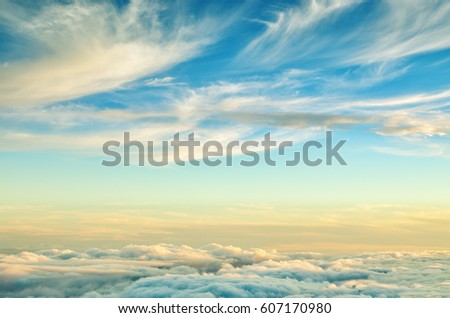 Abstract background with gold and blue colors clouds. Sunset sky above the clouds. Dreamy fantasy background in soft pastel colors .