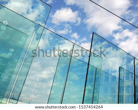 Abstract background with transparent glasses through which you can see the blue sky with clouds. The concept of transparency. #1537454264