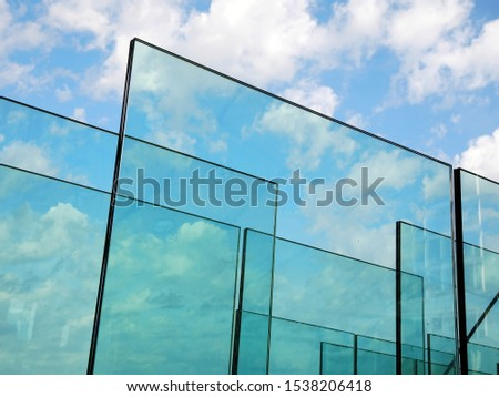 Abstract background with transparent glasses through which you can see the blue sky with clouds. The concept of transparency. #1538206418