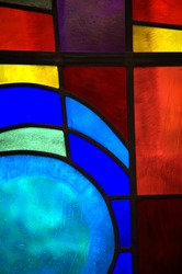 Abstract backlit stained glass window detail with primary colors and shapes