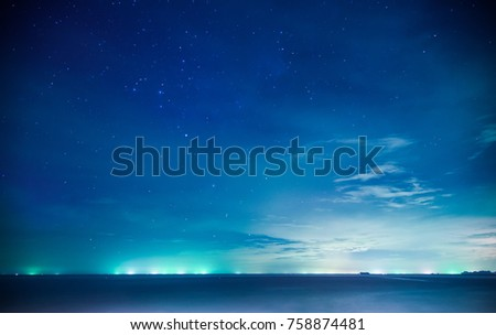 Abstract beautiful night background with blue star sky and seascape with green light from many boat far away. #758874481