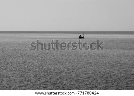 Abstract black and white and minimal concept image of lonely fishing boat floating on the sea. (Selective focus) #771780424