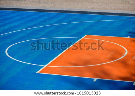 Abstract, blue background of newly made outdoor basketball court in park. Visible asphalt texture, freshly painted lines
